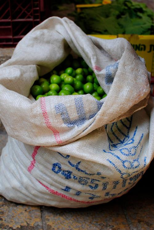 Woven sack of green sour cherries in the market.